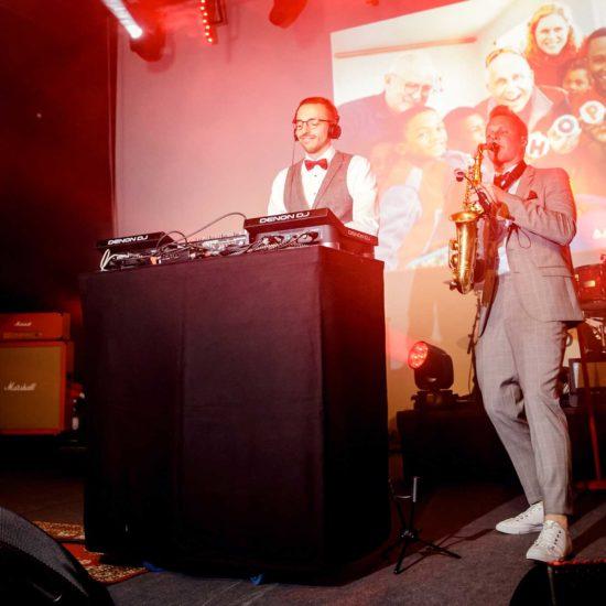 Ein DJ und ein Saxophonist spielen auf einer Party.