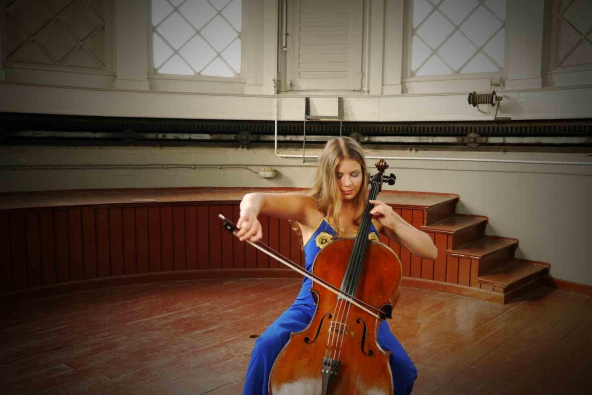 Sofia von Freydorf spielt Cello in einem blauen Kleid vor einer Bühne
