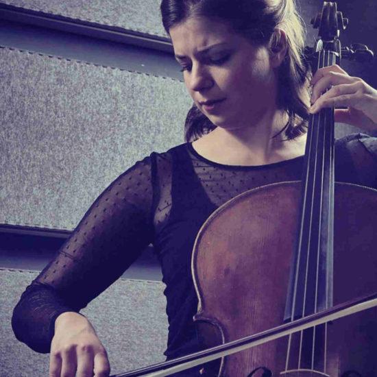 Die Cellistin Sofia von Freydorf spielt in einem schwarzen Kleid auf ihrem Cello
