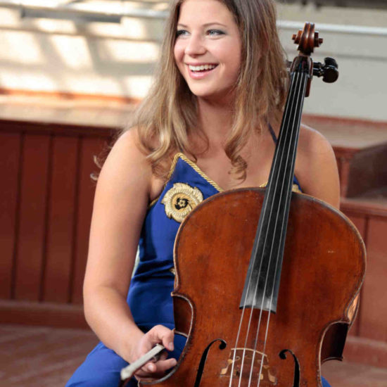 Cellistin Sofia von Freydorf sitzt mit ihrem Cello in einem blauen Kleid vor einer Bühne