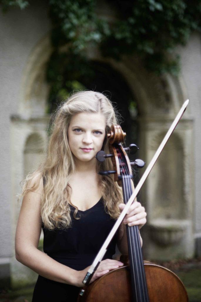 Die Cellistin Alma Stolte steht mit Ihrem Cello in einem schwarzen Kleid vor einem Torbogen
