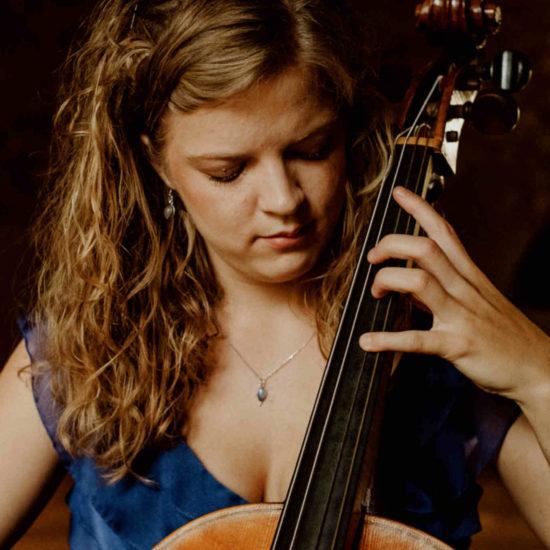 Die Musikerin Alma Stolte spielt auf ihrem Cello in einem blauen Kleid