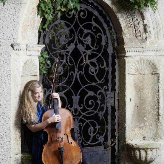 Die Cellistin Alma Stolte sitzt in einem Torbogen und zupft ihr Instrument