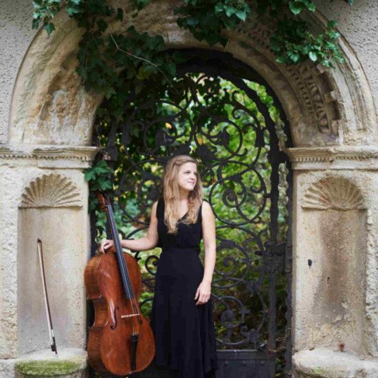 Die Cellistin Alma Stolte steht neben ihrem Cello in einem schwarzen Kleid in einem Torbogen