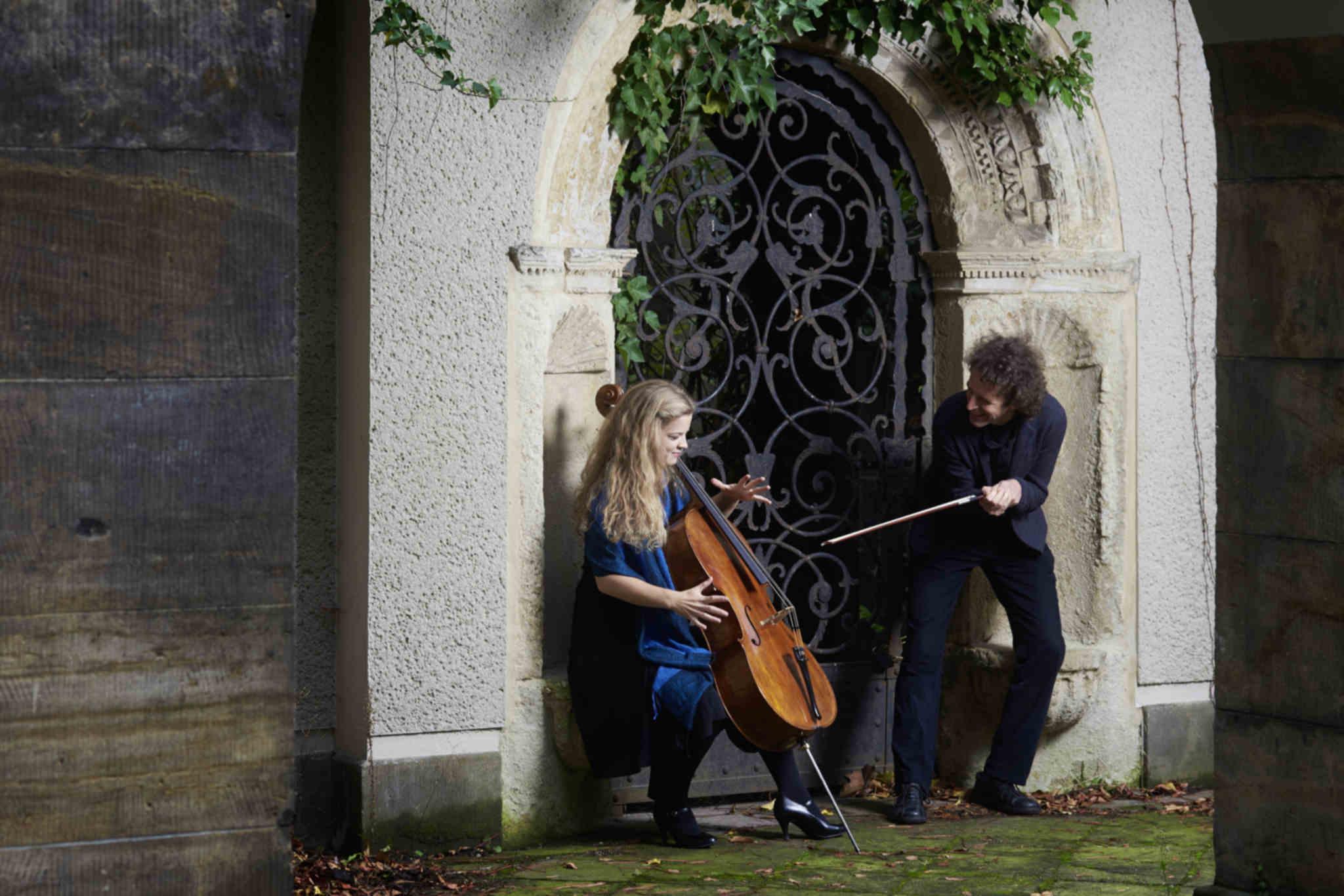 Die Cellistin Alma Stolte sitzt mit Ihrem Cello in einem Torbogen, daneben steht ihr Duo-Partner Pianist Friedemann Stolte und hält ihren Cellobogen