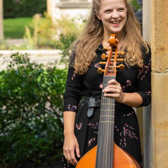 Die Gambenspielerin und Cellistin Alma Stolte lehnt hinter Ihrer Gambe lächelnd an eine Sandsteinsäule
