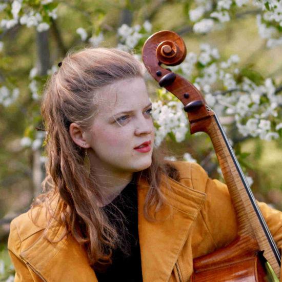 Die Cellistin Alma Stolte steht mit ihrem Cello in einer orangefarbenen Lederjacke vor einem blühenden Obstbaum