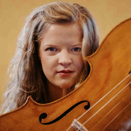 Die Cellistin Alma Stolte steht hiner einem Cello
