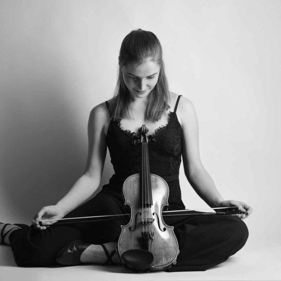 Die Geigerin Charlotte Thiele sitzt auf dem Boden und hält ihre Violine vor dem Körper