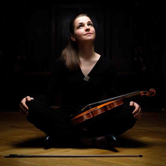 Die Violinistin Charlotte Thiele sitzt im Schneidersitz und hat ihre Violine auf dem Schoß