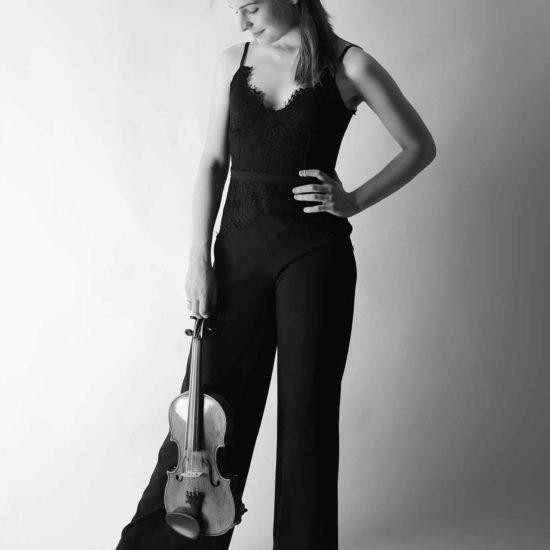 Die Geigerin Charlotte Thiele hält ihre Geige in der Hand