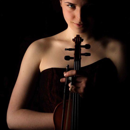 Die Geigerin Charlotte Thie hält ihre Geige vor dem Körper