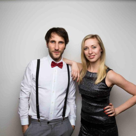 Das Duo Livestyle in der Besetzung Christin Krause (Gesang) und Sascha Hunermund (Gitarre) steht vor einer grauen Wand