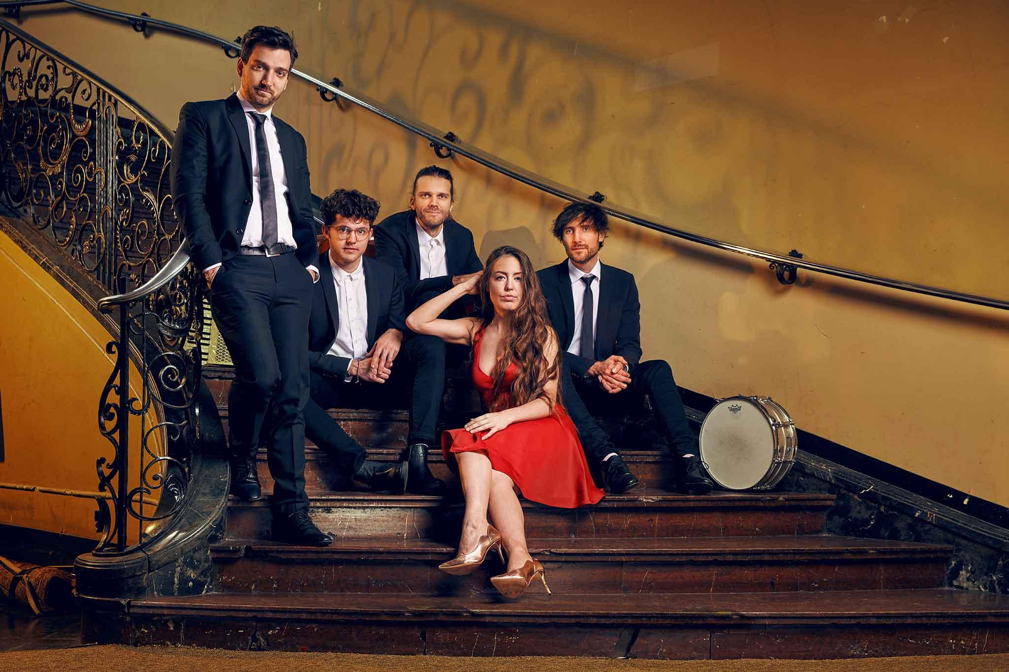 Chansons mit der Band DÉJÀ VU sitzt in einem alten Treppenhaus