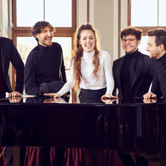 Die Leipziger Jazzband DÉJÀ VU steht an einem Flügel und lacht in die Kamera