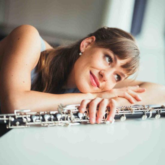 Die sächsische Oboistin Elisabeth Beckert lehnt auf einem Fensterbrett und hält eine Oboe