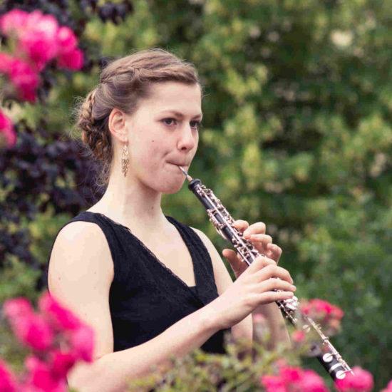 Die Oboistin Elisabeth Beckert spielt in einem scharzen Kleid hinter einer Blumenhecke ihr Instrument