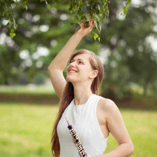 Die Dresdner Musikerin Elisabeth Beckert greift in einem weißen Kleid nach einem Zweig und hält in der anderen Hand eine Oboe