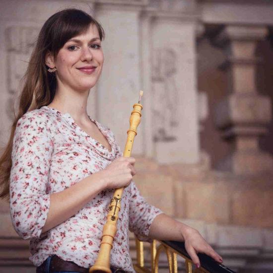 Die Dresdner Musikerin Elisabeth Beckert steht mit ihrer Barockoboe vor einem Geländer