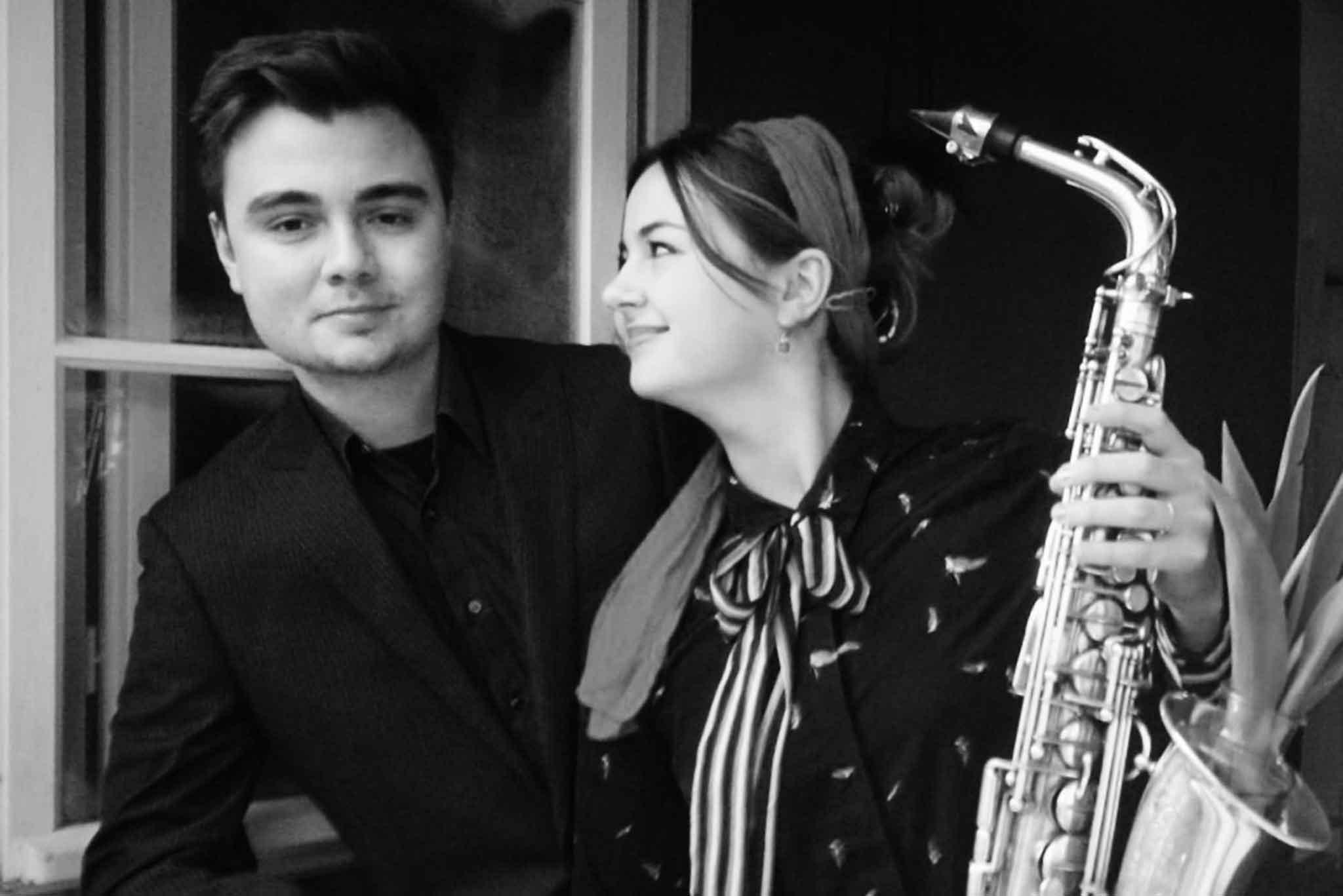 Die Saxophonistin Lina Peters und ein Pianist schauen durch ein Fenster