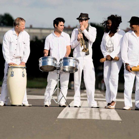 Die Latinband Mi Solar posiert in weißer Kleidung auf einer Straße