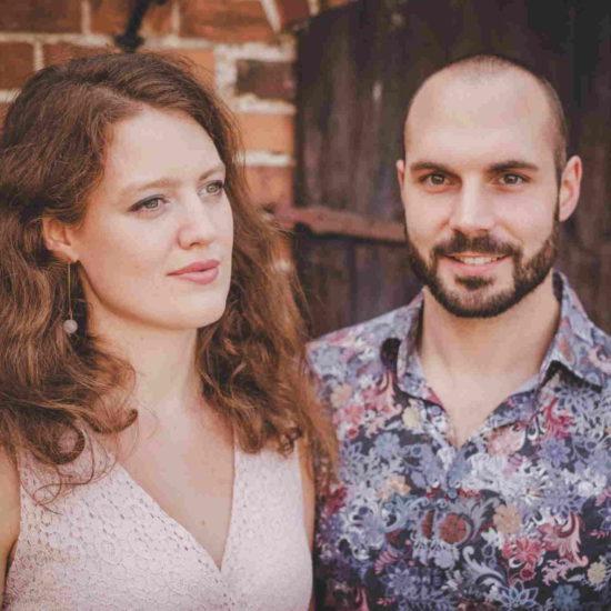 Das Duo SARAH und LUCA steht vor einem alten Gebäude