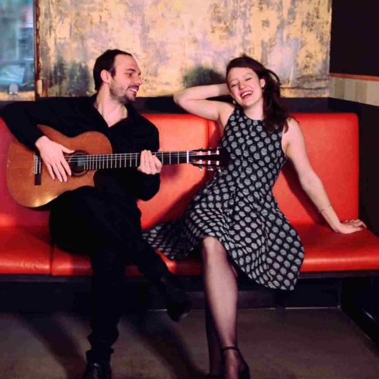 SARAH und LUCA sitzen auf einem roten Sofa und stimmen sich auf einen Liveauftritt ein