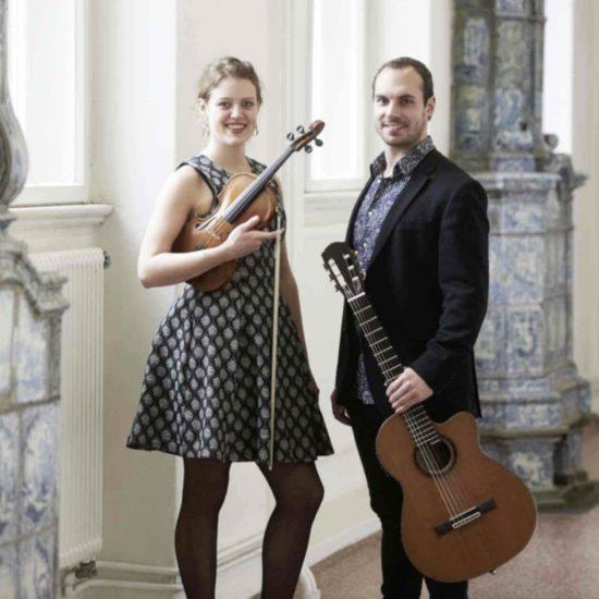 Die Musiker des Duos SARAH und LUCA stehen mit Violine und Gitarre in einem Gang