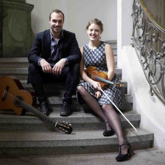 Die Musiker SARAH und LUCA sitzen mit Violine und Gitarre auf einer Treppe