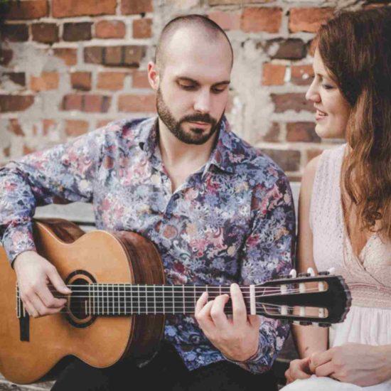SARAH und LUCA sitzen vor einer Backsteinmauer und präsentieren Livemusik mit Gesang und Gitarre