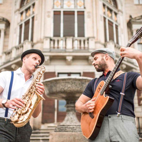 Der Saxophonist und Gitarrist des Jazzduos Schooko-Duo stehen vor Schloss Albrechtsberg in Dresden
