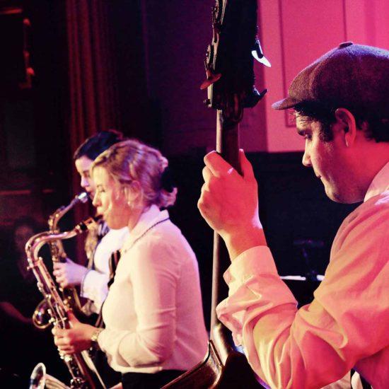 Zwei Saxophonistinnen und ein Kontrabassist muszieren auf einer Bühne