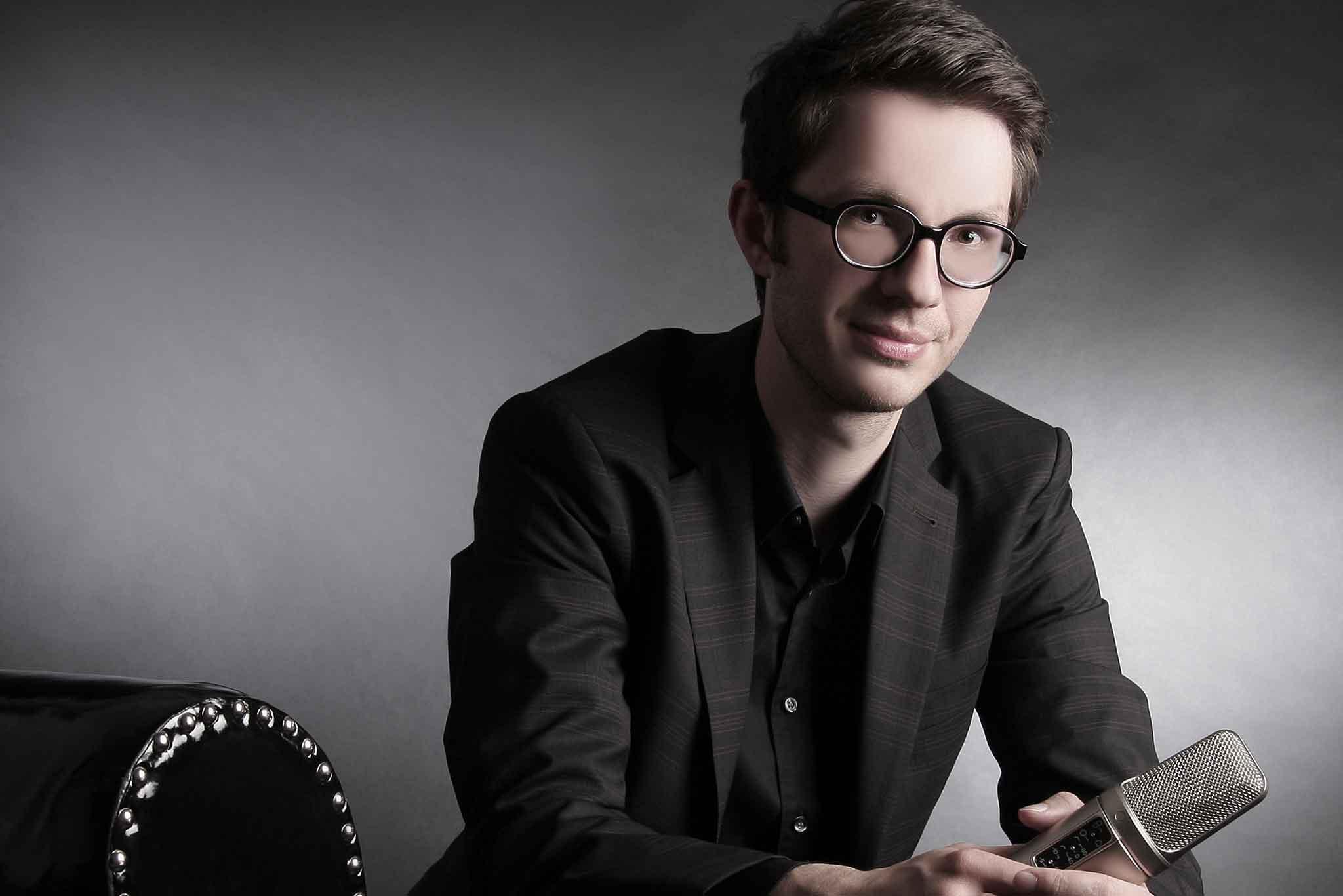 Der Sprecher Tobias Moeck hält ein Mikrophon in der Hand.
