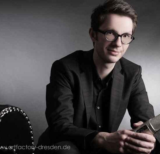 Profisprecher Tobias Moeck sitzt auf einer Couch und hält ein Mikrofon in der Hand