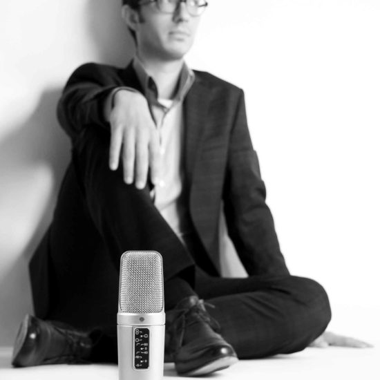 Synchronsprecher Tobias Moeck lehnt an einer Wand und vor ihm steht ein Mikrofon