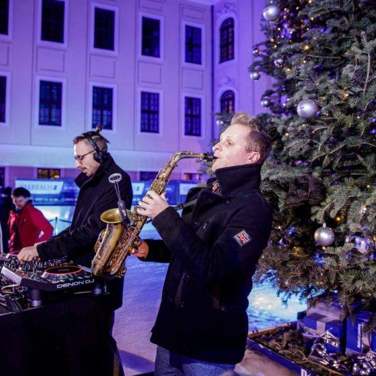 DJ mit Saxophon Kenduro&Schoof spielen vor einem Weihnachtsbaum auf einer Eisfläche