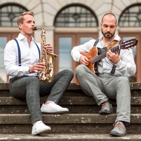 Ein Saxophonist und ein Gitarrist sitzen auf Treppenstufen
