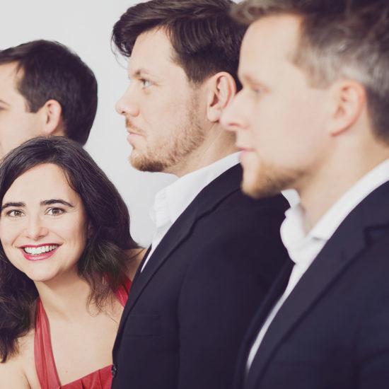 Die Sängerin der Hochzeitsband Adlips schaut in die Kamera, während ihre Livemusiker nach links schauen