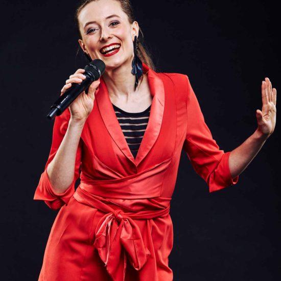 Die Sängerin Jasmin Graff hält ein Mikrofon in der Hand und lächelt in die Kamera