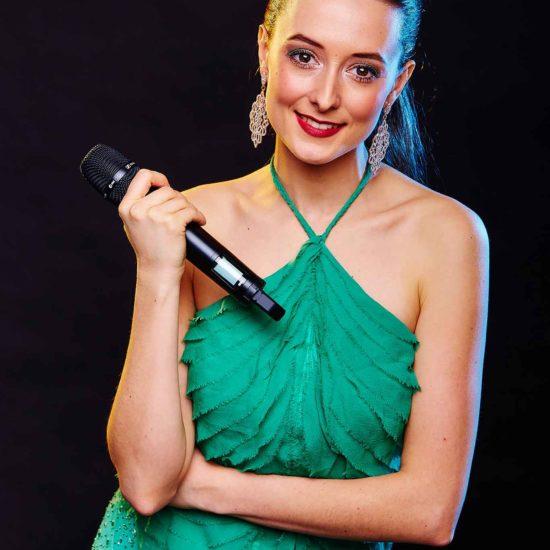 Die Livemusikerin Jasmin Graff hält ein Mikrofon in der Hand und schaut in die Kamera