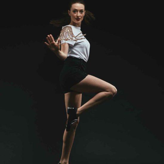 Die Tap Dancerin Jasmin Graff hat ein Bein angezogen und schaut in die Kamera