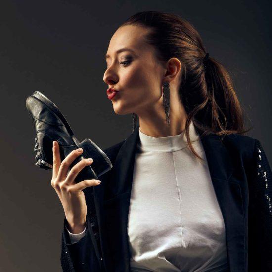 Die Stepptänzerin Jasmin Graff hält einen Tanzschuh in der Hand