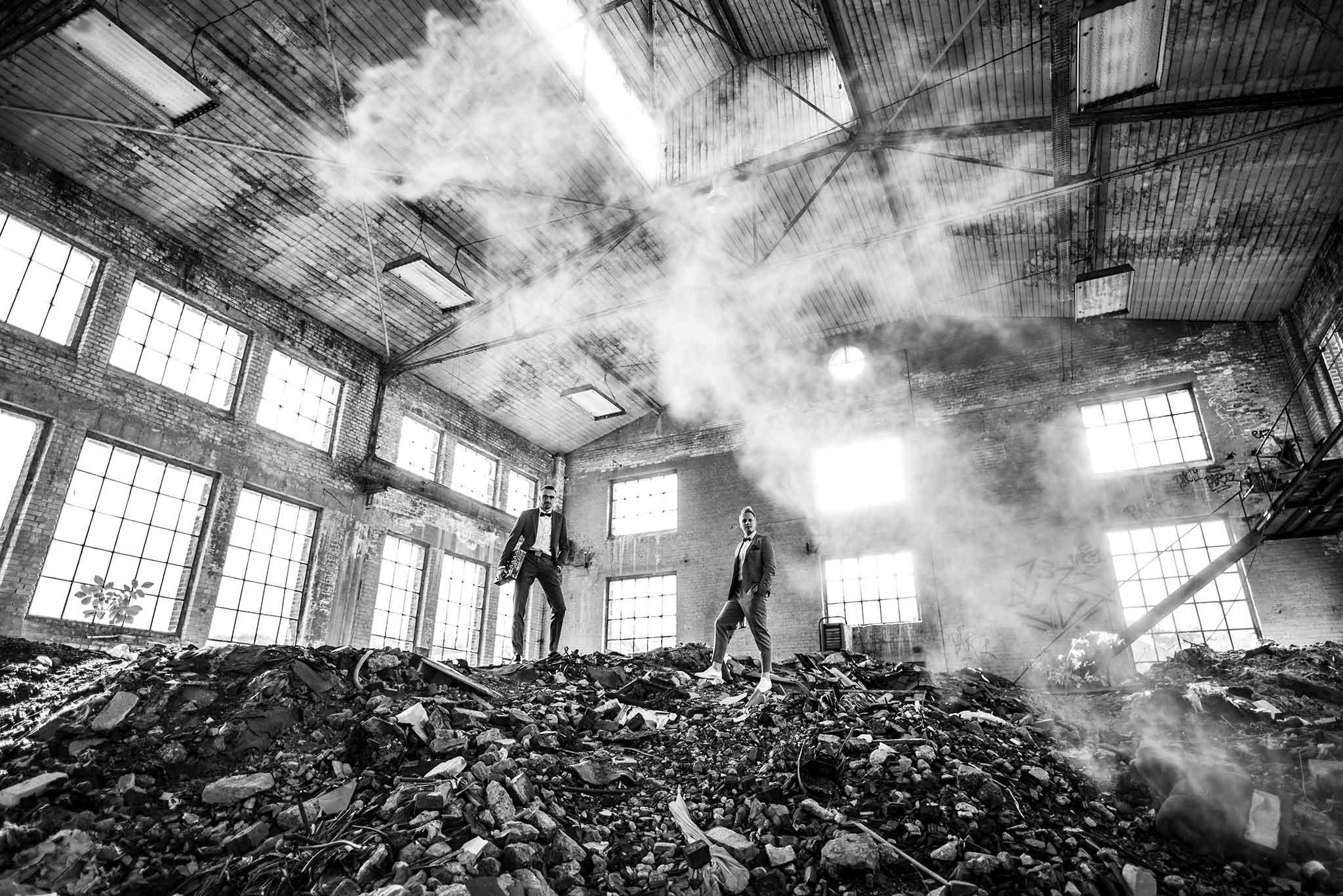 Ein Saxophonist und ein DJ stehen in einer alten Fabrikhalle.