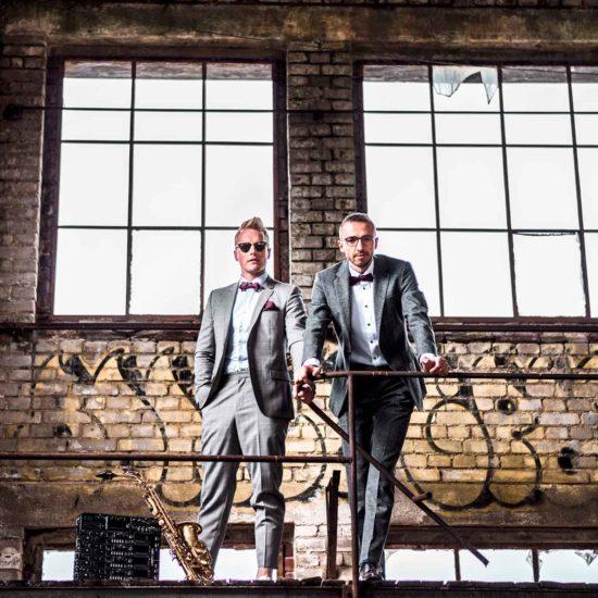 Ein Saxophonist und ein DJ stehen in einer alten Fabrikhalle und lehnen an einem Geländer.
