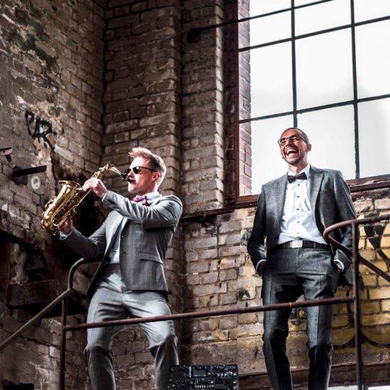 Ein DJ und ein Saxophonist stehen in einer alten Fabrikhalle.