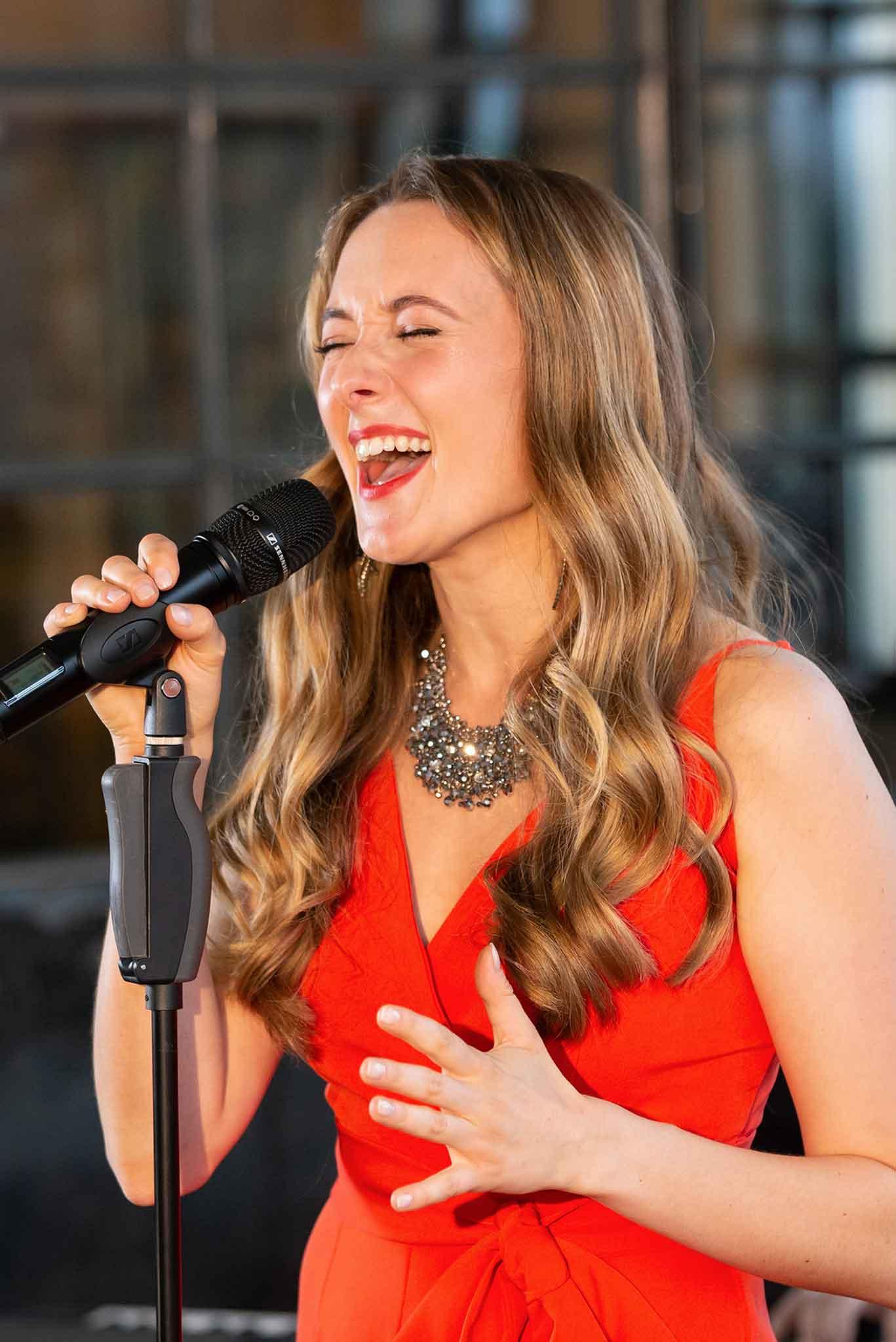 Hochzeitssängerin Jasmin Graff singt energetsich in ein Mikrofon