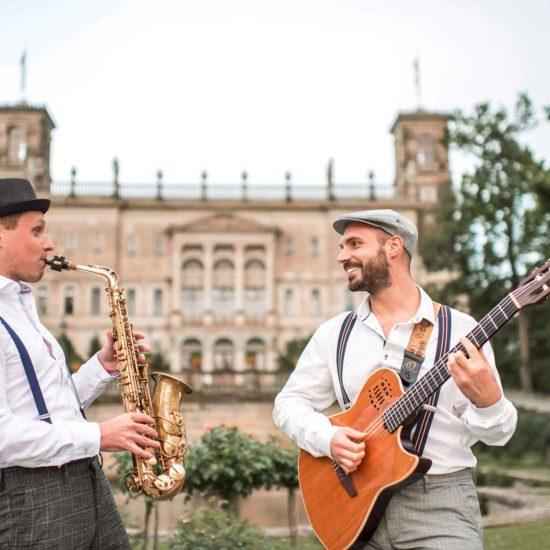 Ein Saxophonist und ein Gitarrist stehen vor Schloss Albrechtsberg in Dresden und spielen Livemusik