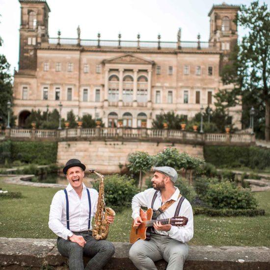 Das Schooko-Duo (Saxophon und Gitarre) sitzt vor Schloss Albrechtsberg in Dresden