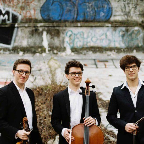Zwei Geiger und ein Cellist lächeln in die Kamera