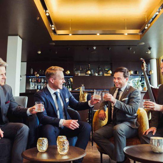 Die Hochzeitsband Swing Department sitzt in einer Hotelbar und prostet sich zu